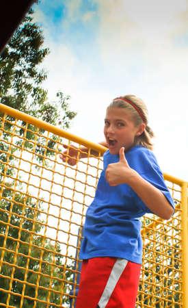 Confident preteen girl climbing playground equipment in park