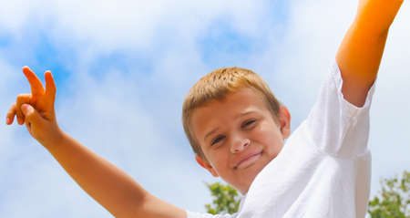 confident preteen boy with victory sign against cloudy sky Stock Photo