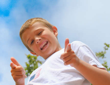 confident, happy boy with pointing fingers against blue sky