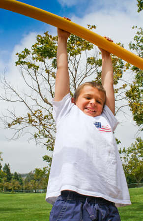 Happy youth hanging from high bar in park against blue sky photo