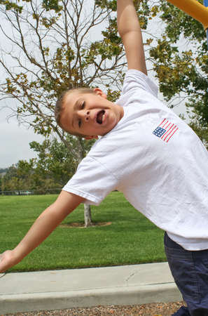 happy Boy hanging from one hand from bar in park photo