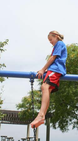 confident Preteen girl sitting on bar above park swing