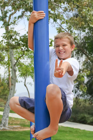 Happy Boy on pole with victory peace sign