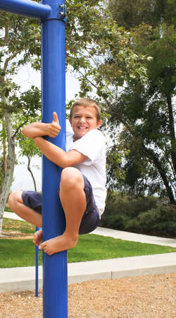 happy Boy on pole with thumbs up sign photo