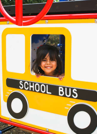 Hispanic Preschooler on playground bus Stock Photo - 15340493