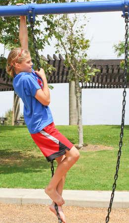 determined teenage girl climbing swing chain Stock Photo