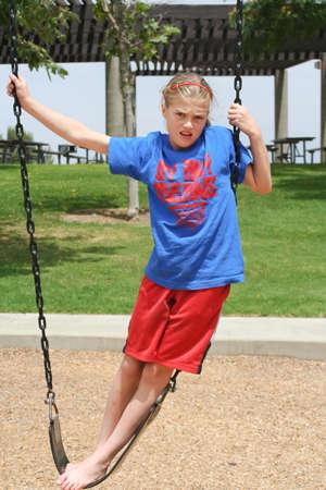 Angry teenage girl standing defiantly on park swing