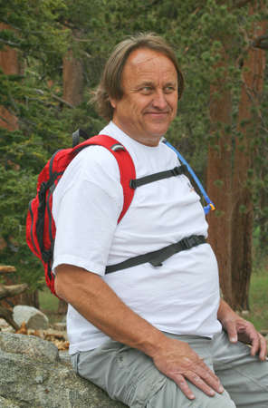 Happy resting male baby-boomer hiker photo