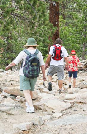 Three boulder jumping baby boomer hikers