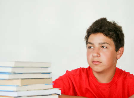 Daydreaming male teen with book stack to study