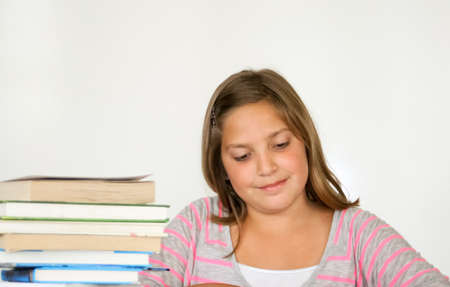 Perky, smiling preteen girl studying with book stack Stock Photo - 15243539