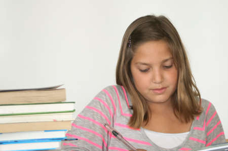 3  Pretty preteen student studying with book stack