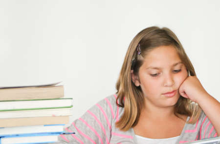 Bored-looking pretty preteen girl studying with book stack Stock Photo - 15243514