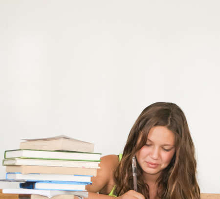 Pretty female teenage student studying and writing photo