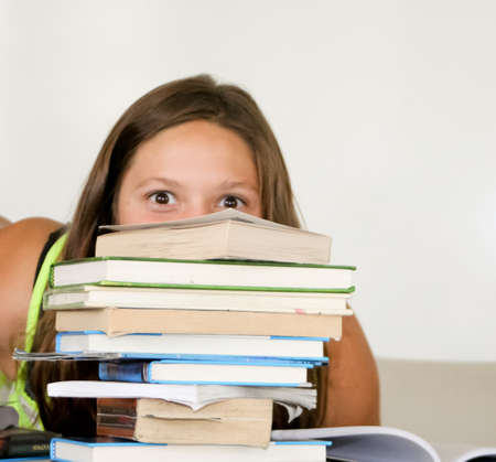 Playful teenage girl peeking over tall stack of books Stock Photo - 15243511