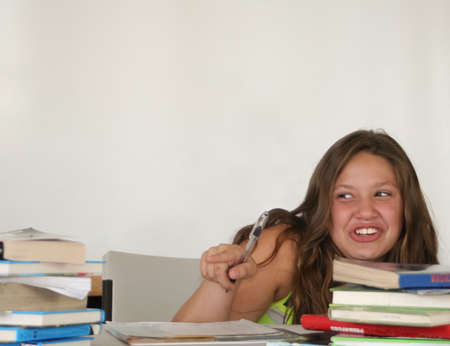 Pretty giggling teen student pointing at tall book stack photo