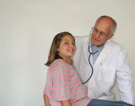 Older male doctor with pretty preteen female patient Stock Photo