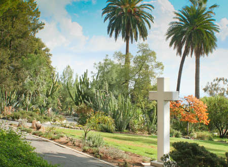 Tall white cross overlooking manicured lawn
