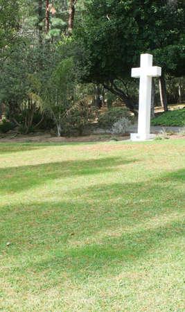 White cross on green grassy hill