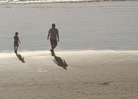 Father and son shadows on a white beach Stock Photo