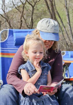Grandma reading to happy female toddler in park