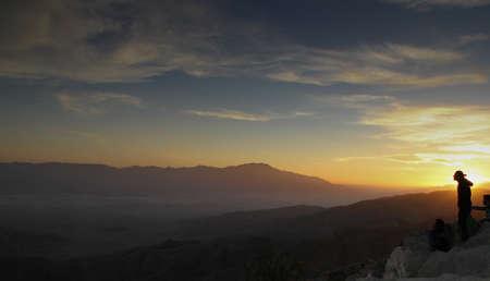 Dark desert sunset with sun shadowed by lone hiker on hilltop
