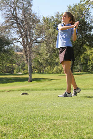 Pretty Female teen golfer just after tee-off