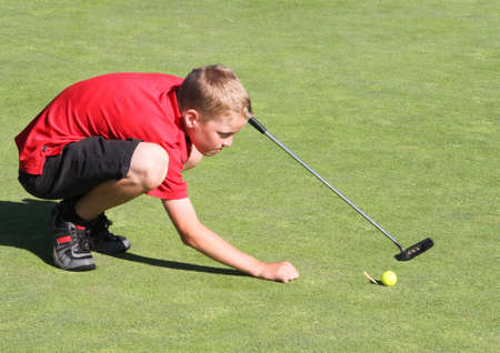 Young male golfer kneeling to line up putt