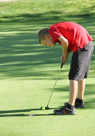 Preteen male golfer putting final shot 版權商用圖片