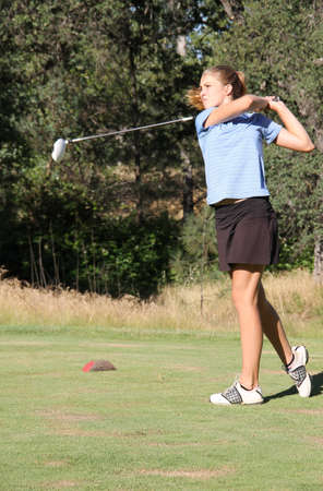 Female Teen golfer after swing with club over shoulder
