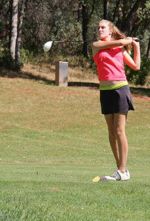 Pretty female teen golfer watching ball fly
