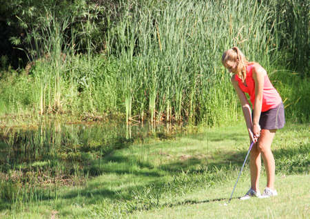 Female teen golfer chipping away from pond