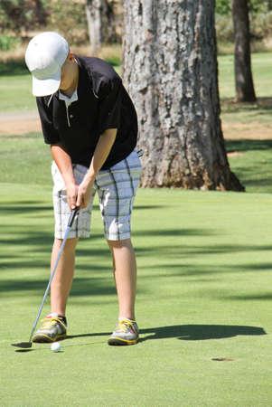 Male teen golfer shooting four foot putt