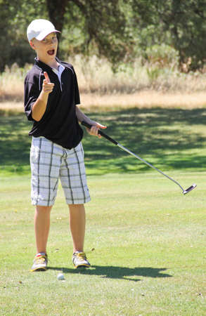 Young male golfer pointing happily toward camera