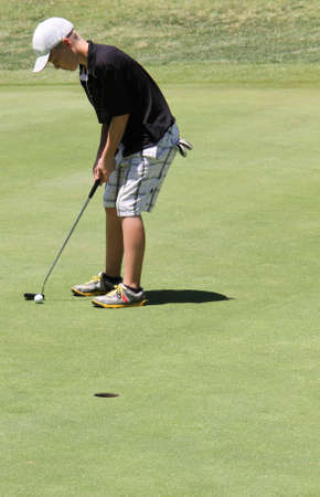 Male teen golfer expertly shooting ten foot putt Standard-Bild