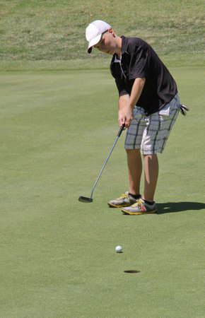 Male teen golfer sinking ten foot putt Standard-Bild