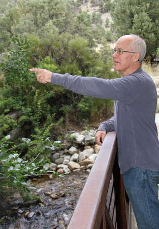 Senior male standing on footbridge over stream 版權商用圖片