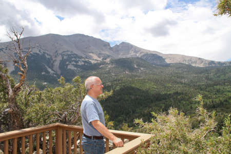senior male standing on mountain overlook seeing trees and sky