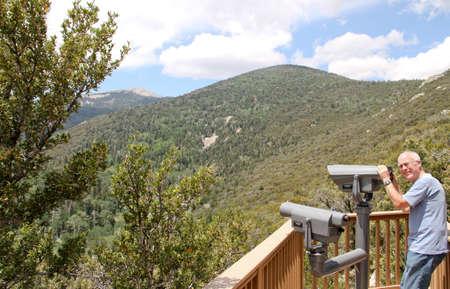 LTerer Mann, der auf Berg übersehen mit Teleskop zu sehen, Bäume und Himmel Standard-Bild - 30632116