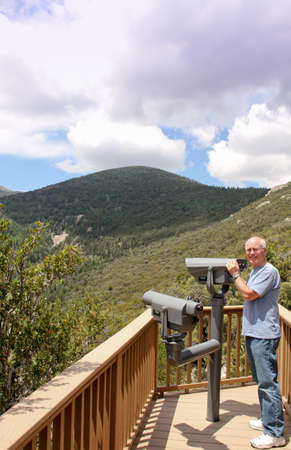 senior male standing on mountain overlook with telescope seeing trees and sky
