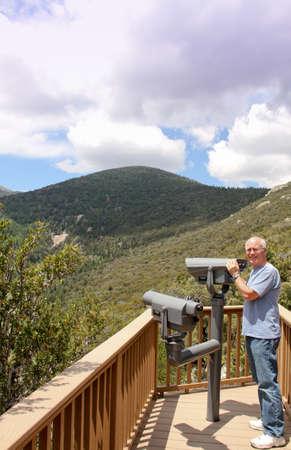 LTerer Mann, der auf Berg übersehen mit Teleskop zu sehen, Bäume und Himmel Standard-Bild - 30632117