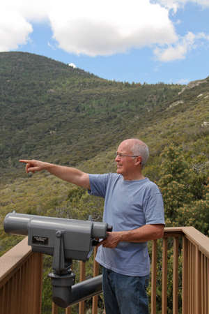 LTerer Mann, der auf Berg übersehen mit Teleskop zu sehen, Bäume und Himmel Standard-Bild - 30632118