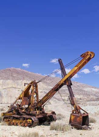 vintage yellow rusting mining backhoe abandoned in Nevada desert Imagens