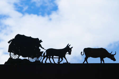 black cut out covered wagon and cow figures silhouetted against cloudy blue sky Stock Photo