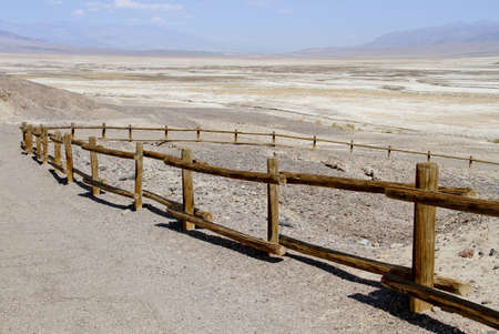 winding death valley dirt road with log rail fence