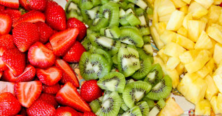 plate of cut strawberries kiwis and pineapple appetizer
