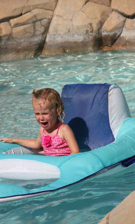 angry crying female toddler floating on raft in swimming pool