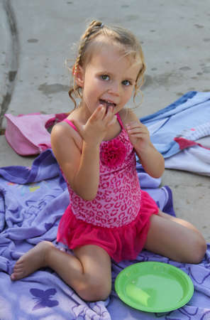 smiling pretty female toddler eating at poolside party