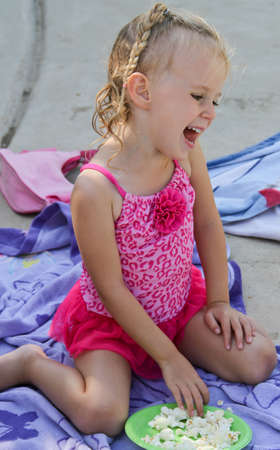 giggling happy female toddler eating at family poolside picnic