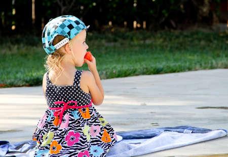 female toddler eating watermelon near swimming pool 版權商用圖片